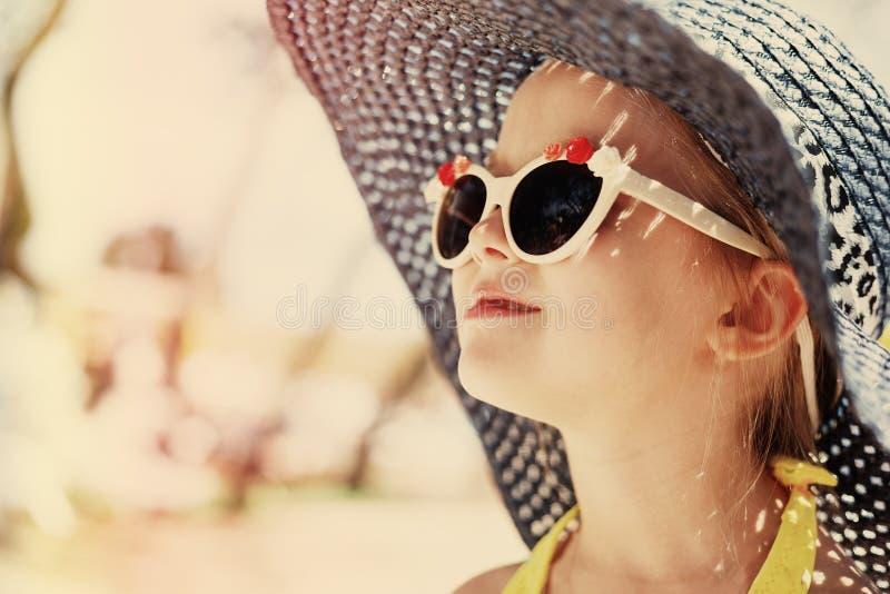 Entzückendes kleines Mädchen am Strand während der Sommerferien stockfotografie
