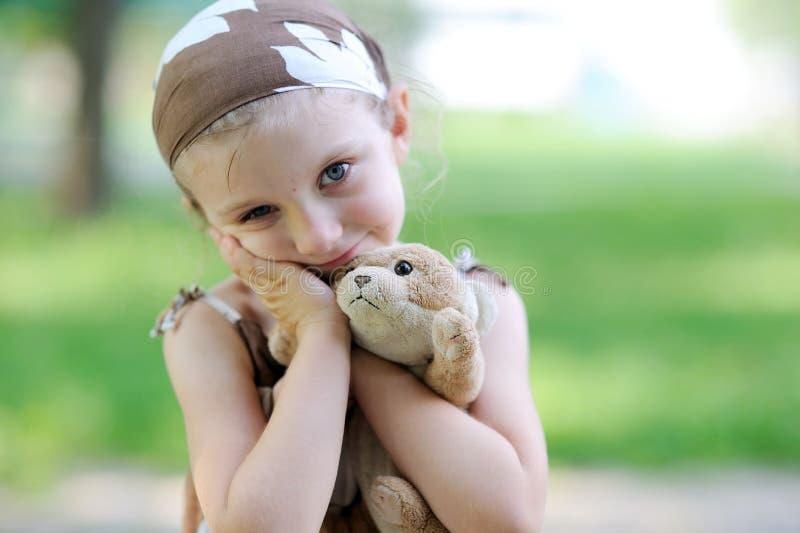Entzückendes kleines Mädchen umarmt ihr Spielzeug stockfotos