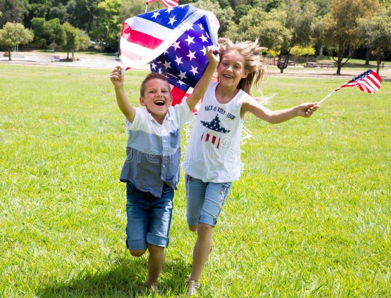Entzückendes kleines Mädchen und Junge laufen auf dem hellgrünen Gras, das draußen amerikanische Flagge am schönen Sommertag hält stockbilder