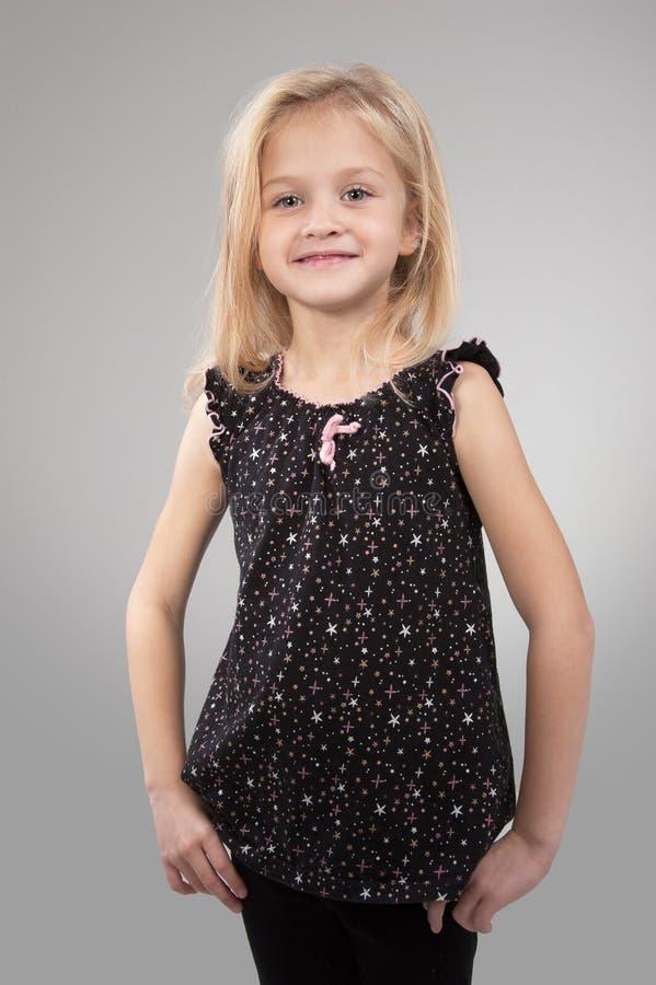 Entzückendes kleines Mädchen, welches die Kamera betrachtet stockfotografie