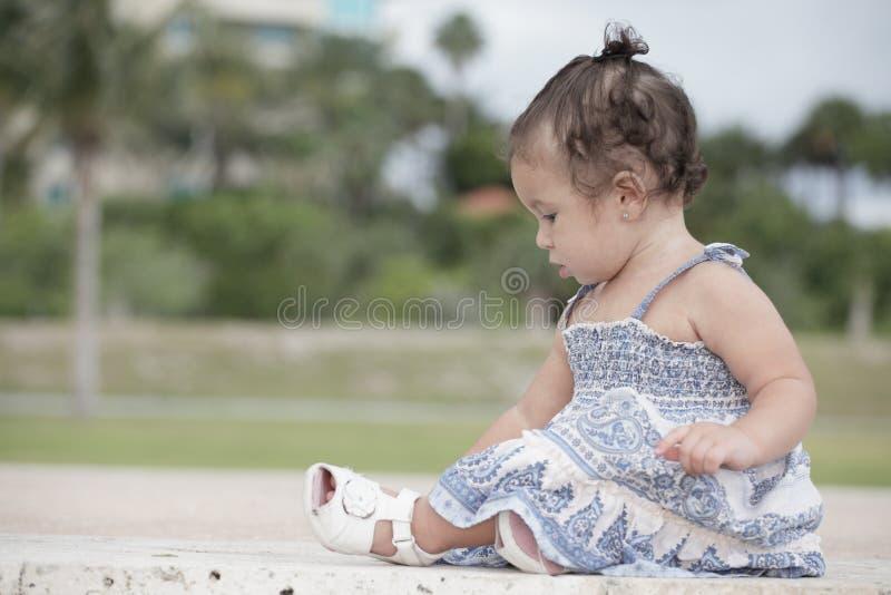 Entzückendes Kleinkind, das im Park sitzt stockfoto