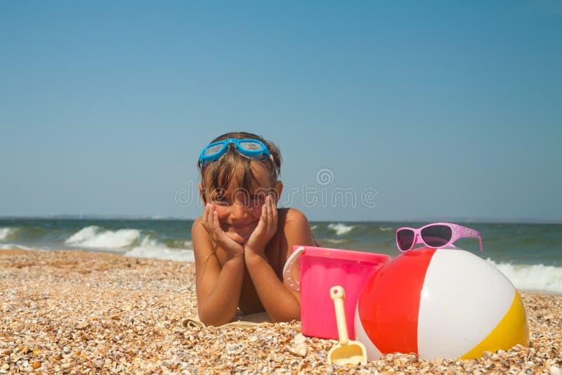 Entzückendes Kleinkindmädchen, das mit Spielwaren auf Sandstrand spielt stockbilder