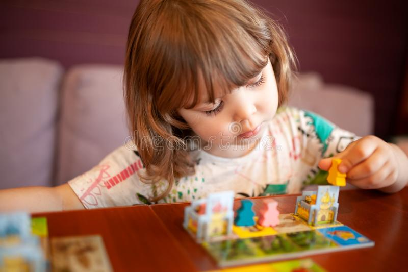 Entzückendes Kleinkindmädchen, das zuhause Brettspiel spielt lizenzfreies stockbild