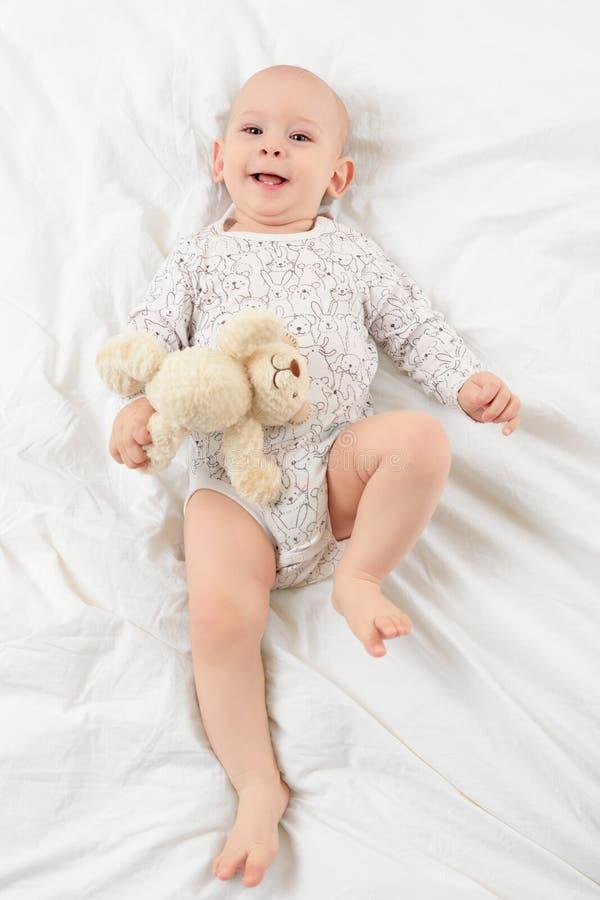 Entzückendes lächelndes Baby mit den blauen Augen, die auf einem Bett mit seinem Liebling liegen, füllte das Teddybärspielzeug an stockbilder