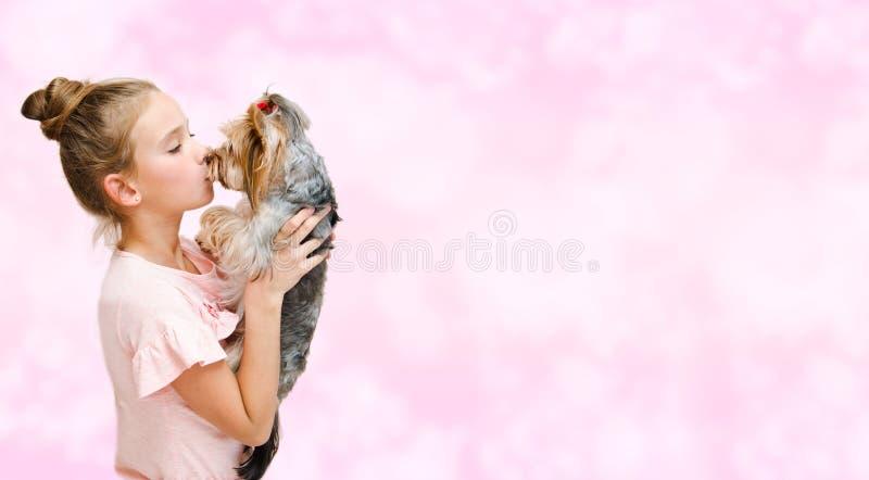 Entzückendes lächelndes glückliches Kind des kleinen Mädchens, das mit Welpenyorkshire-Terrier spielt lizenzfreies stockbild