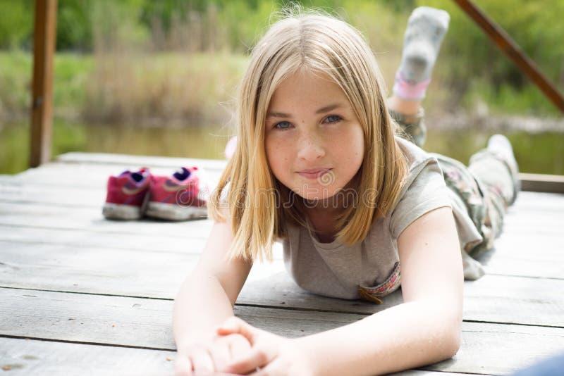Entzückendes lächelndes jugendlich Mädchen, das auf ihrem Magen auf einer Holzbrücke liegt lizenzfreies stockfoto