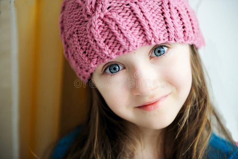 Entzückendes lächelndes Kindmädchen im rosafarbenen gestrickten Hut lizenzfreies stockfoto