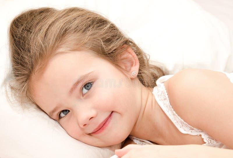 Entzückendes lächelndes kleines Mädchen oben aufgeweckt stockbild