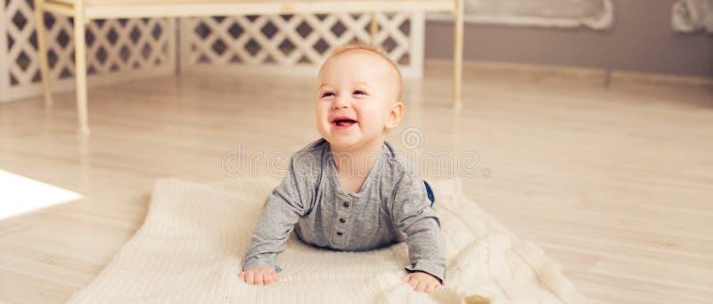 Entzückendes lachendes Baby im sonnigen Schlafzimmer Neugeborenes entspannendes Kind Kindertagesstätte für Kleinkinder Familienmo lizenzfreie stockfotografie