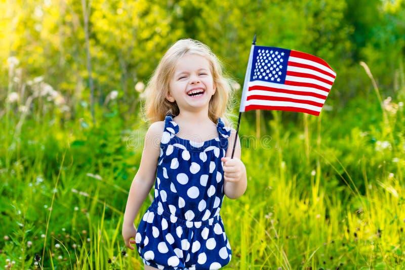 Entzückendes lachendes blondes kleines Mädchen, das amerikanische Flagge hält stockfotografie