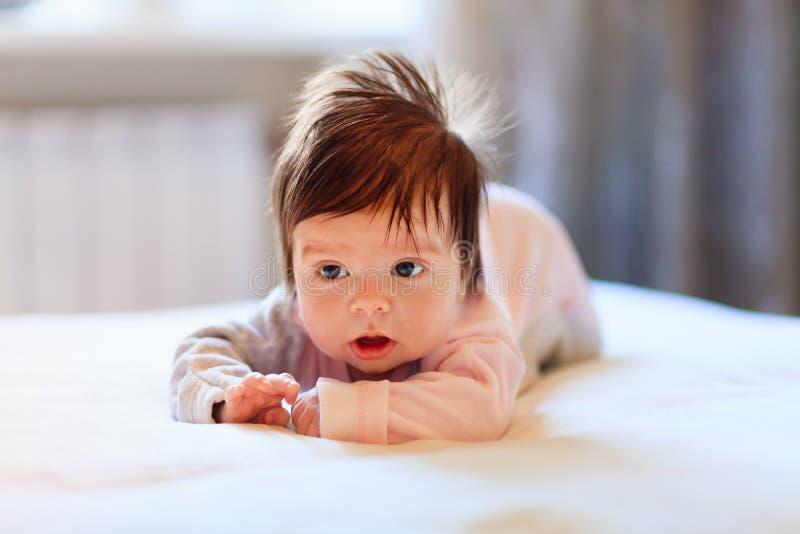 Entzückendes Mädchen auf dem Bett stockbilder