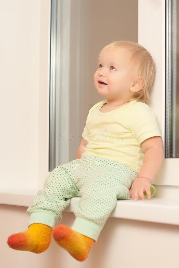Entzückendes Mädchen, das auf dem Fensterrahmen sitzt lizenzfreies stockbild
