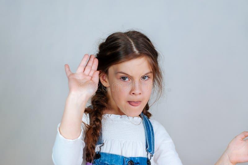 Entz?ckendes M?dchen, das auf leeren Raum, emotionales Portr?t zeigt L?chelndes Kind im Denimoverall, der Verkaufsrabatt darstell stockbild
