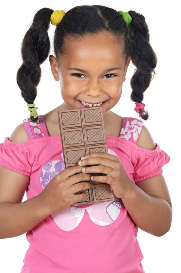 Entzückendes Mädchen, das Schokolade isst stockfotografie