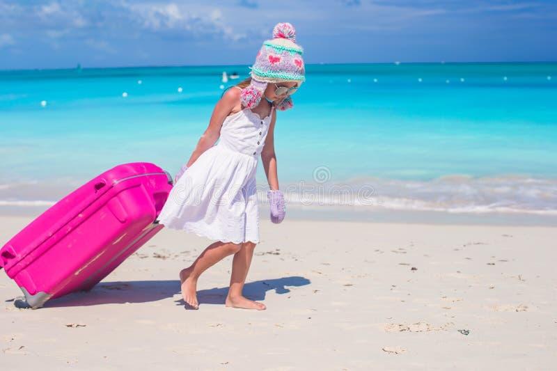 Entzückendes Mädchen im Winterhut und -handschuhen gehend mit Gepäck auf Strand stockbild
