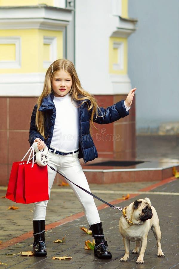 Entzückendes Mädchen mit Einkaufstaschen und ihrem Hund stockfoto
