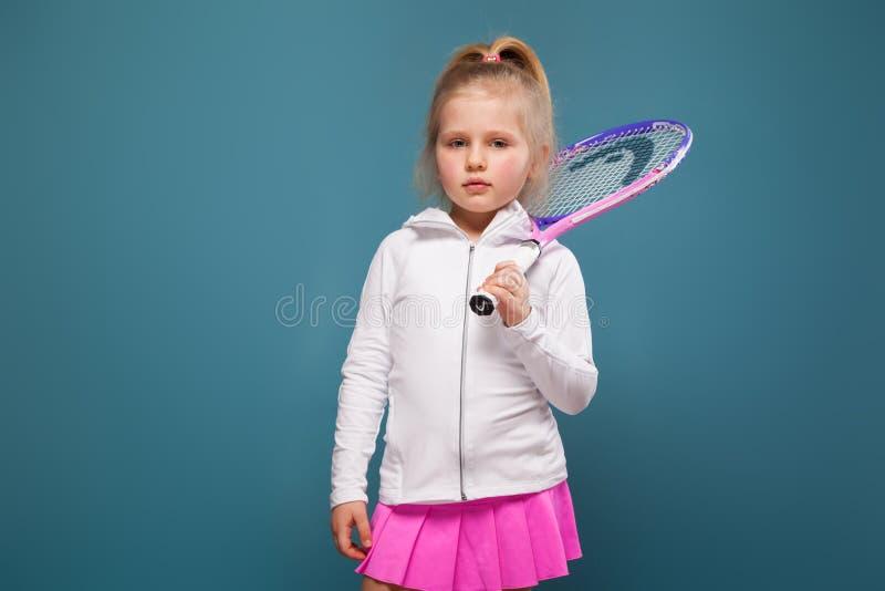 Entzückendes nettes kleines Mädchen im weißen Hemd, in der weißen Jacke und im rosa Rock mit Tennisschläger lizenzfreie stockfotos