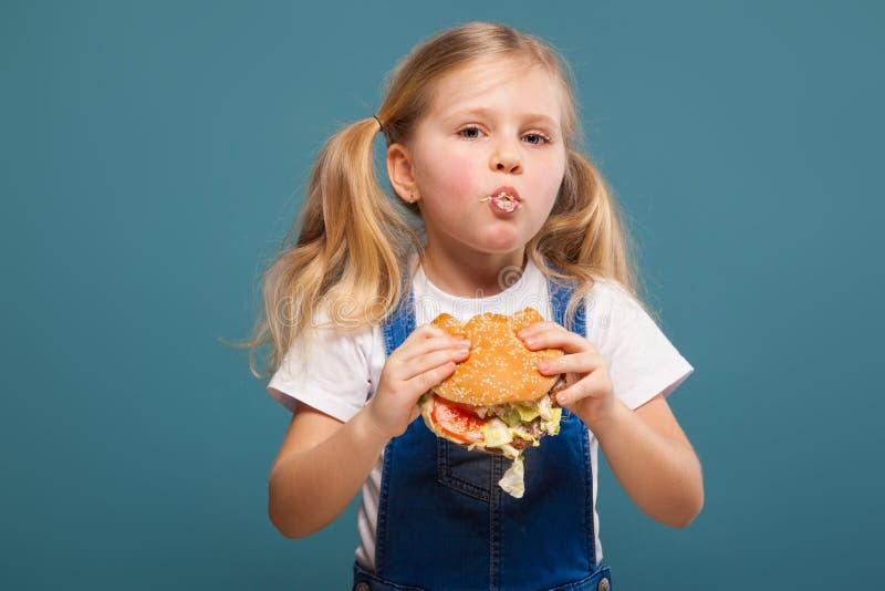 Entzückendes nettes kleines Mädchen im weißen Hemd- und Baumwollstoffoverall mit Hamburger stockfotografie