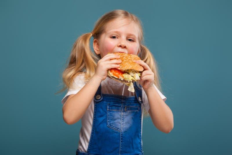Entzückendes nettes kleines Mädchen im weißen Hemd- und Baumwollstoffoverall mit Hamburger lizenzfreies stockfoto