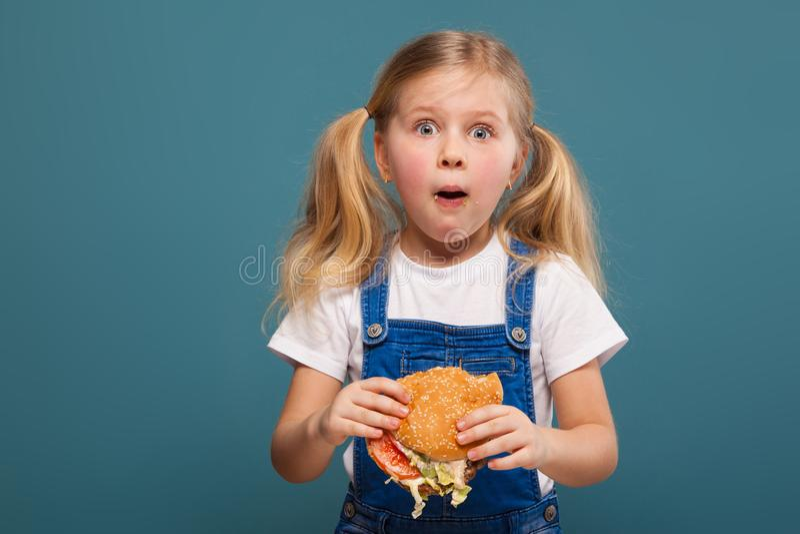 Entzückendes nettes kleines Mädchen im weißen Hemd- und Baumwollstoffoverall mit Hamburger lizenzfreie stockfotografie