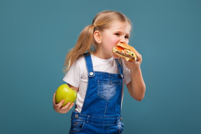 Entzückendes nettes kleines Mädchen im weißen Hemd- und Baumwollstoffoverall mit Hamburger und Apfel lizenzfreie stockfotos