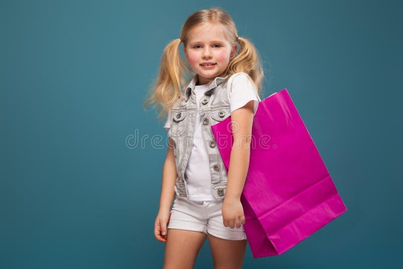 Entzückendes nettes kleines Mädchen im weißen Hemd, weiße Jacke und weiße kurze Hosen halten purpurrote Papiertüte lizenzfreies stockfoto