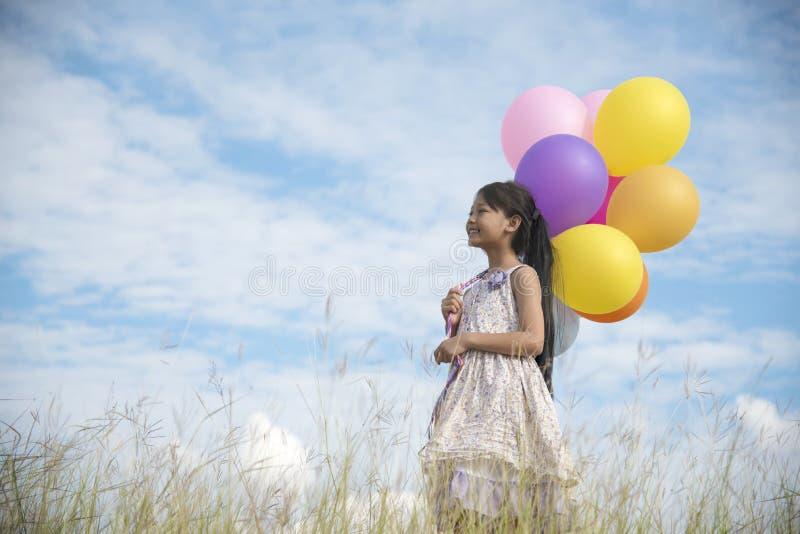 Entzückendes nettes Mädchen, das bunte Ballone mit dem blauen Himmel hält stockfotografie