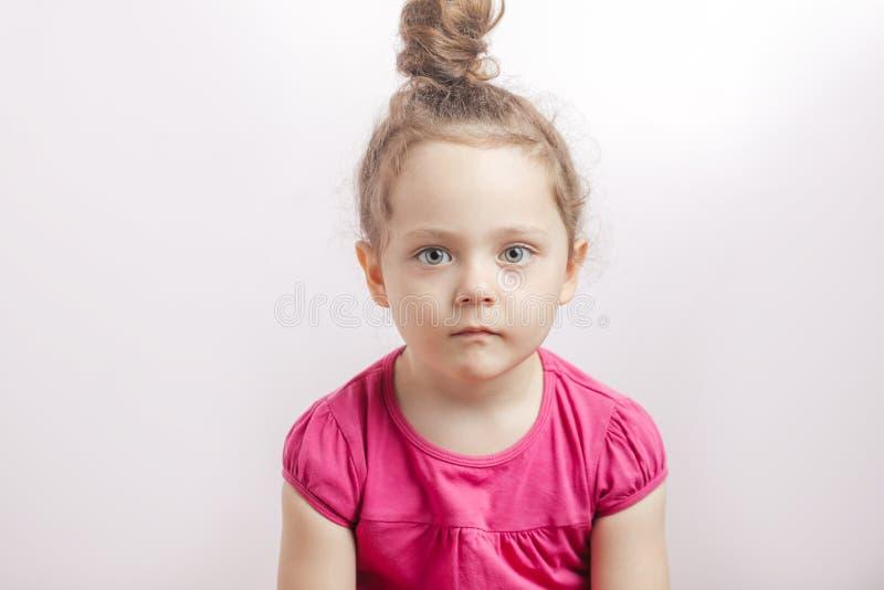 Entzückendes nettes Mädchen mit dem Haarbrötchen und ernstem Gesicht, welche die Kamera betrachten lizenzfreies stockbild