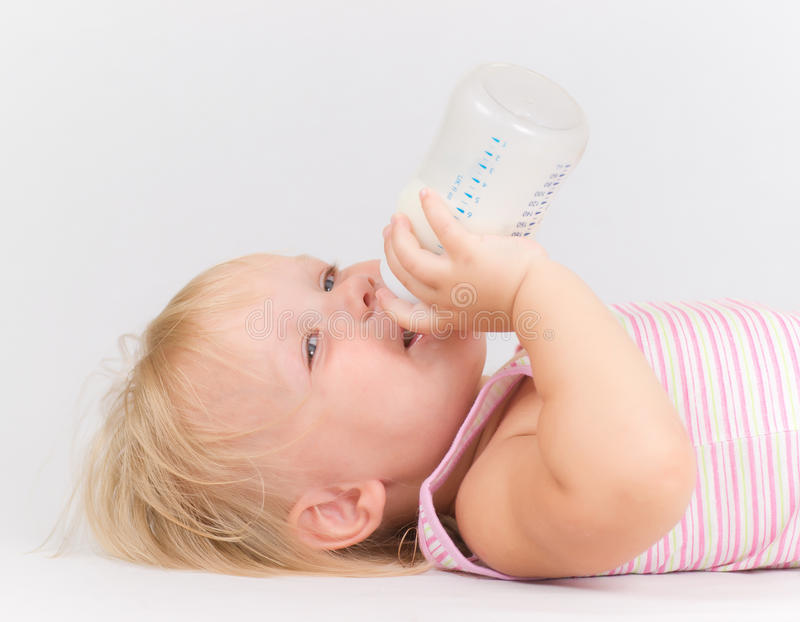 Entzückendes Schätzchen, das Milch von der Flasche isst lizenzfreie stockfotos