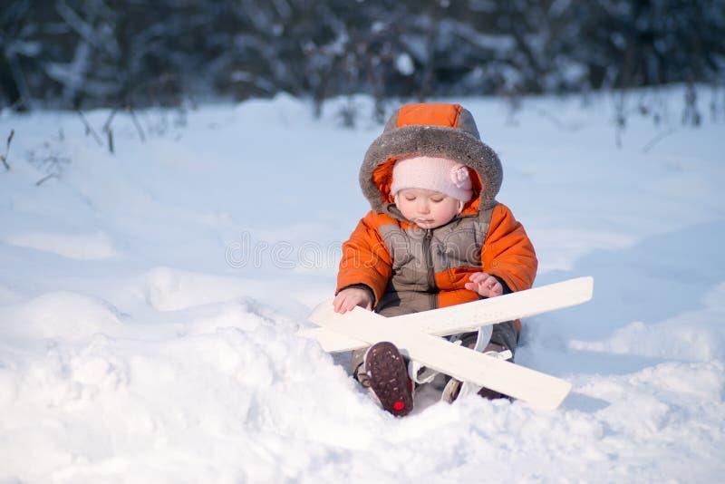 Entzückendes Schätzchen Sitzen Auf Schnee Mit Ski Lizenzfreie Stockfotos