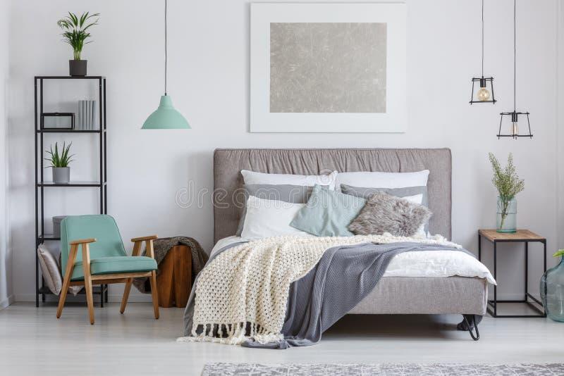 Entzückendes Schlafzimmer mit tadellosem Stuhl lizenzfreie stockbilder