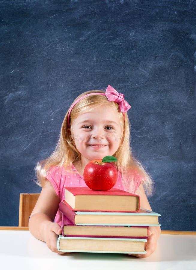 Entzückendes Schulmädchen, das Bücher und Apfel hält lizenzfreies stockbild