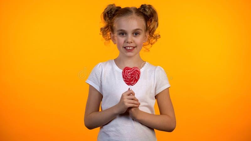 Entzückendes Schulmädchen, das Herz-förmigen Lutscher, glückliches Kind, Süßigkeiten hält lizenzfreie stockfotografie