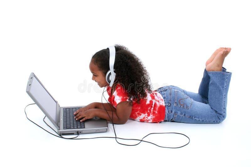 Entzückendes sechs Einjahresmädchen, das auf Fußboden mit Laptop-Computer sitzt lizenzfreie stockbilder