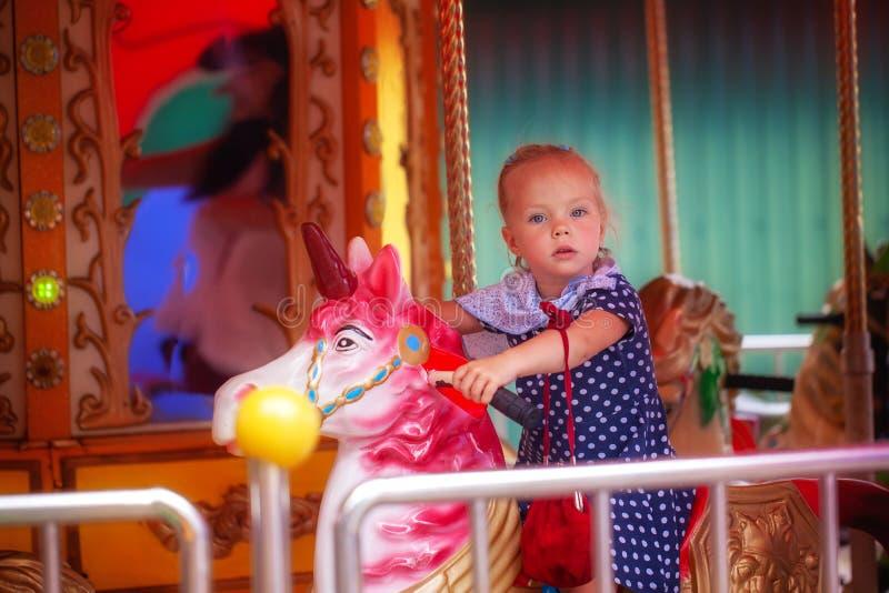 Entzückendes Tupfenkleiderreiten des kleinen Mädchens n auf einem fröhlichen gehen Karussellpferd draußen lizenzfreie stockfotos