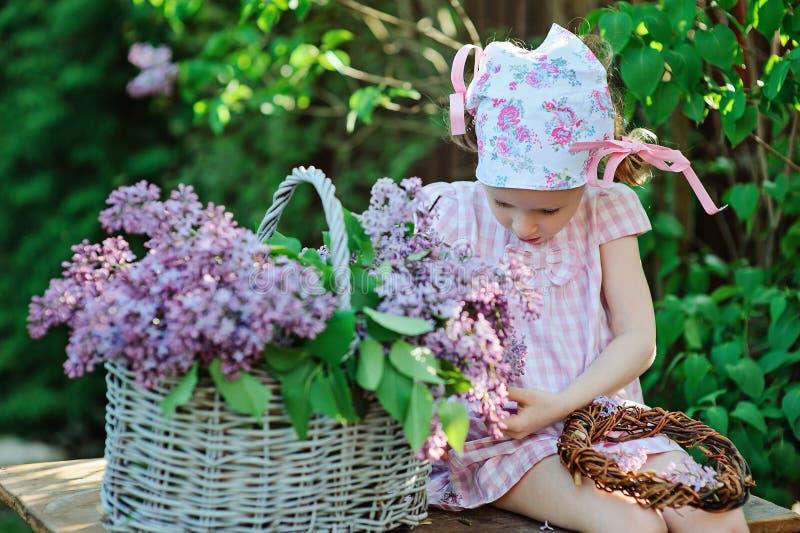 Entzückendes Vorschülermädchen im rosa Plaidkleid, das im Frühjahr lila sonnigen Garten des Kranzes macht stockfoto