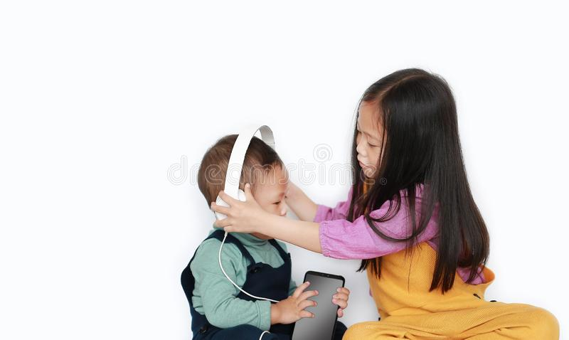 Entz?ckende asiatische ?ltere Schwester und kleine der Bruder, die zu teilt, genie?t h?rende Musik mit Kopfh?rern durch den Smart lizenzfreies stockfoto