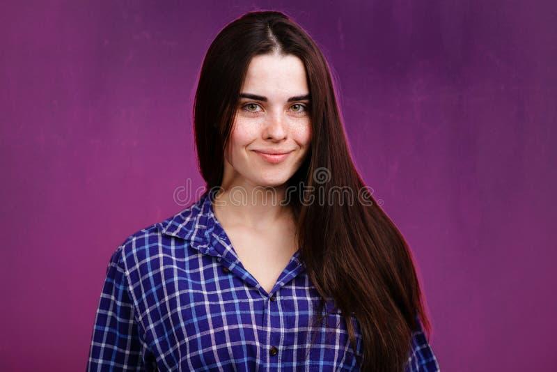 Entz?ckende junge Frau, die auf Kamera und dem L?cheln schaut lizenzfreies stockfoto