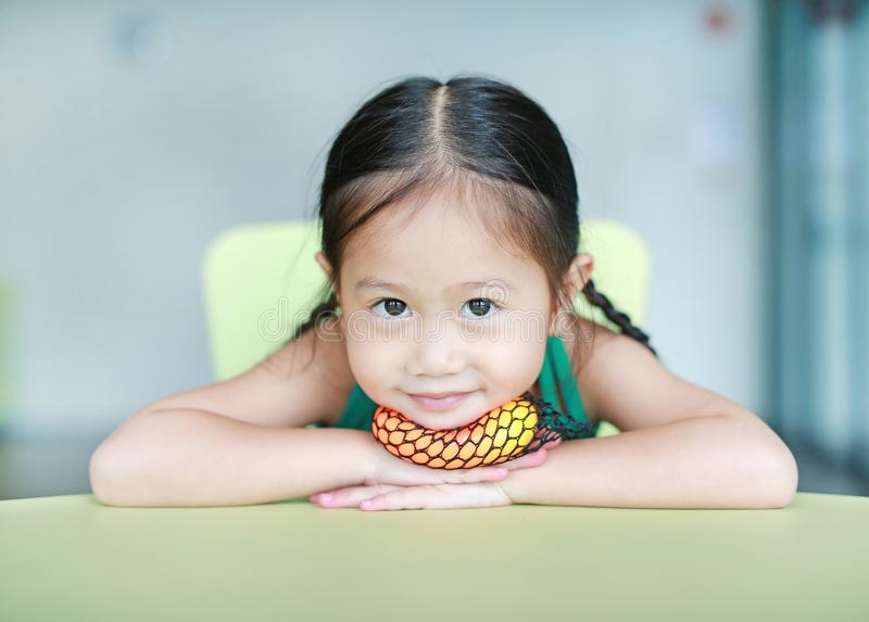 Entz?ckendes kleines asiatisches Kinderm?dchen, das Gummispielzeug im Kinderraum liegt und spielt lizenzfreies stockbild