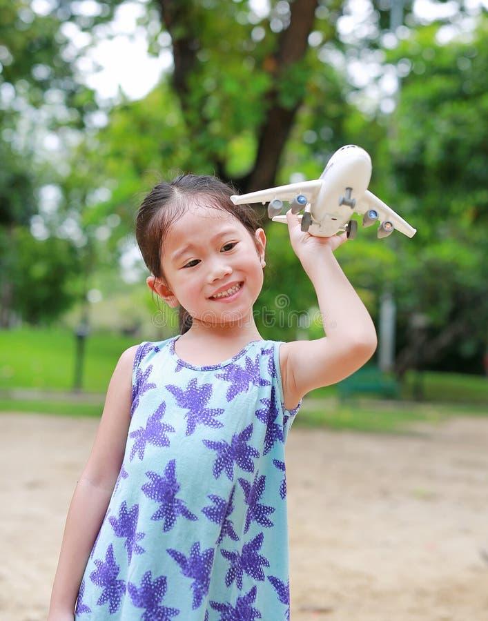 Entz?ckendes kleines asiatisches Kinderm?dchen, das mit einem Spielzeugflugzeug im Garten spielt lizenzfreies stockbild