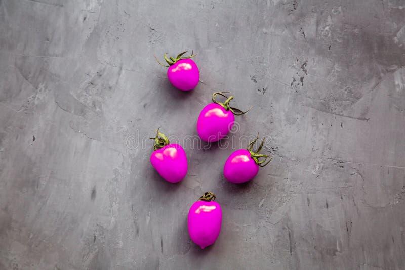 entziehen Sie Hintergrund Neue purpurrote Farbe der Kirschtomaten, die auf einem grauen konkreten Hintergrund, Draufsicht, flache stockbilder