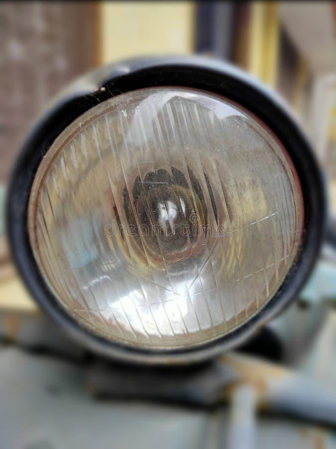Enutformad sparkcykelbillykta med en halogenkula som installeras inom En bild av pannlampan för medelcloseupinfocus arkivbild