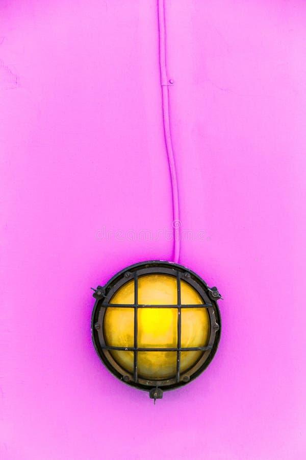 Envíe la luz amarilla del tabique hermético de la lámpara de la cubierta rodeada por un metal aherrumbró marco fijado a una pared imagen de archivo libre de regalías