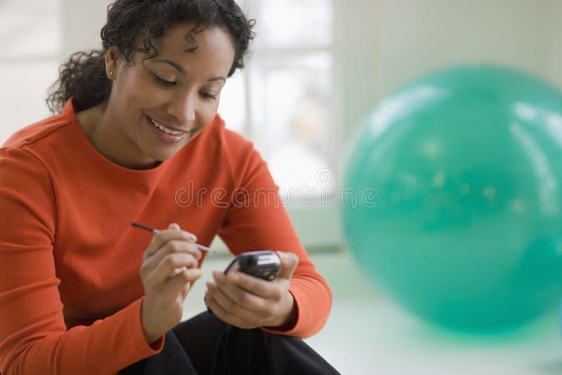 Envío de mensajes de texto hermoso de la mujer en el teléfono celular imagenes de archivo