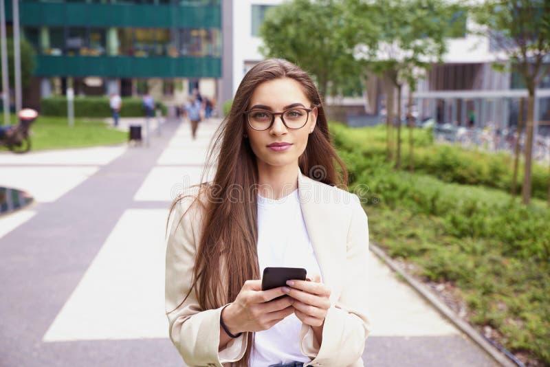 Envío de mensajes de texto joven de la empresaria mientras que camina en la calle en la ciudad imagen de archivo