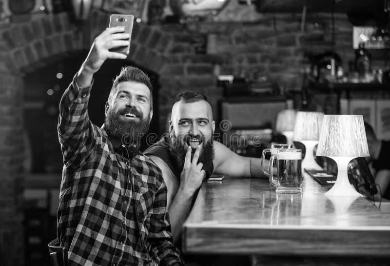 Env?e el selfie a las redes sociales de los amigos Hombre en cerveza de consumici?n de la barra Foto del selfie de la toma para r fotografía de archivo libre de regalías