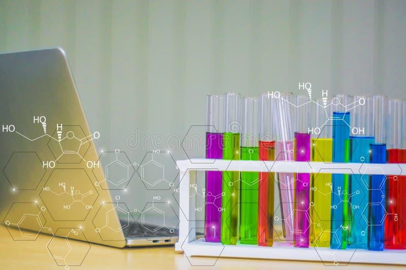 Envase de cristal colorido colocado cerca de un ordenador portátil en laboratorio y un icono químico Con el concepto de investiga foto de archivo libre de regalías