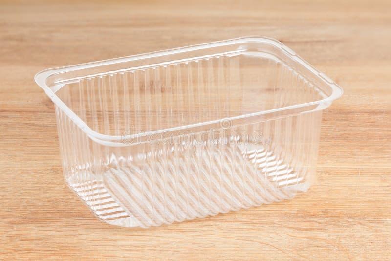Envase de plástico para los productos alimenticios Aislado en de madera fotos de archivo libres de regalías