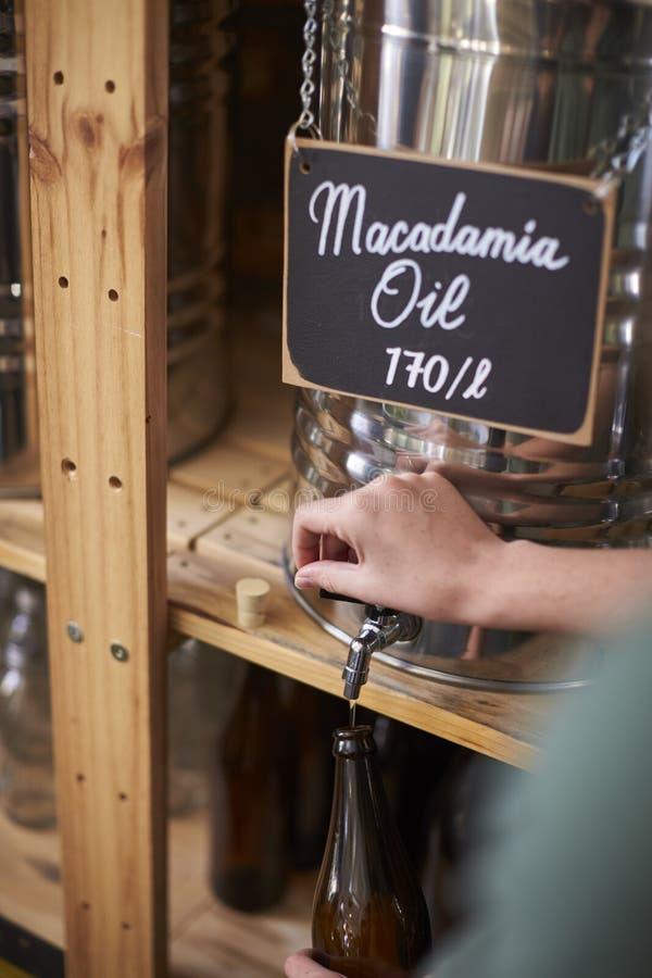 Envase de relleno del hombre con aceite de la macadamia en colmado libre plástico sostenible imagenes de archivo