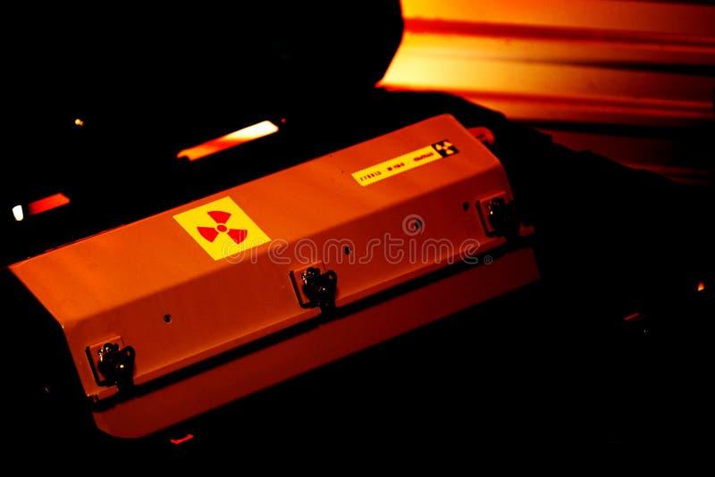 Envase encajonado del metal con la advertencia de la radiación en una caja militar del transporte del grado bajo luz roja fotos de archivo libres de regalías